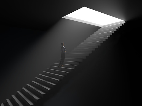 woman climbs the stairs from darkness to light