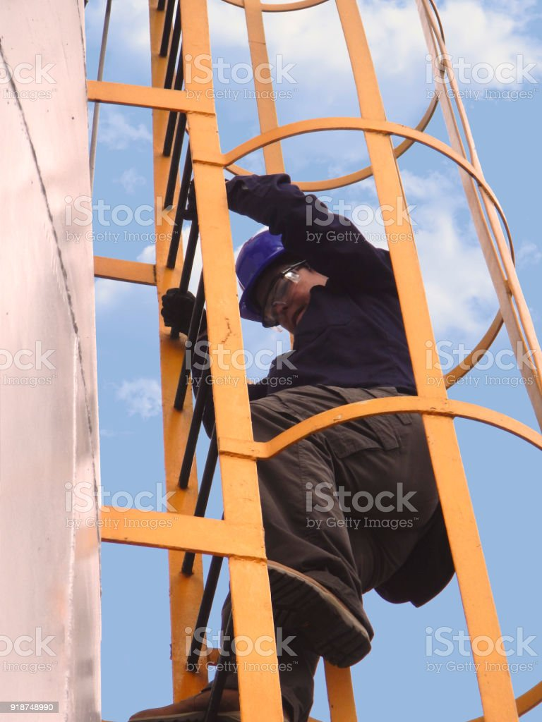 woman climbs the tanks of a refinery stock photo