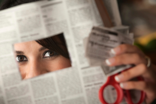Woman Clipping Coupons Out Of Newspaper With Red Scissors Stock Photo - Download Image Now