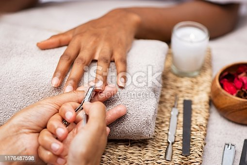 Close up of manicurist hands clipping client nails in a luxury spa. Young woman getting manicure treatment with hands kept on towel.