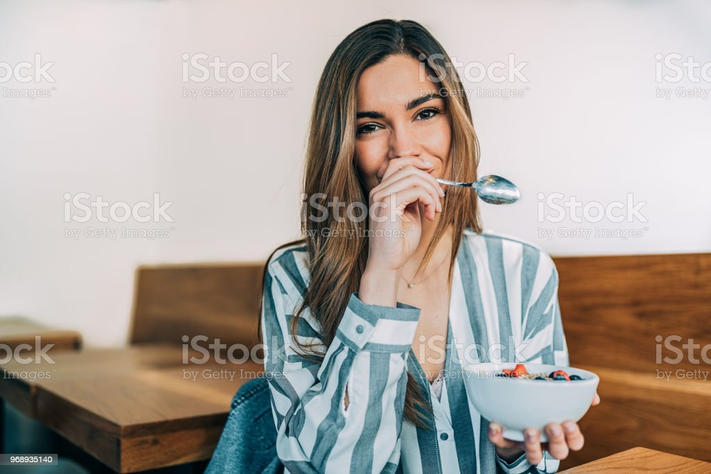 woman close up eating oat and fruits bowl for breakfast stock photo