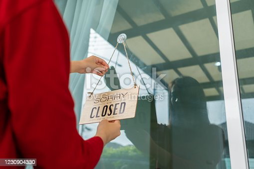 1213432934 istock photo Woman closed store with sign board front door shop, Small business come back turning agian after the situation is resolved. 1230904330