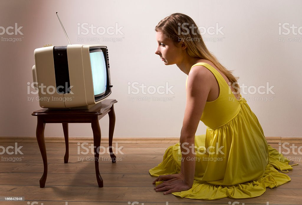 Woman closely watching television stock photo
