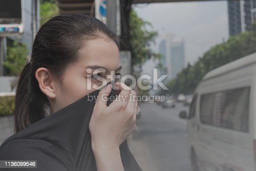 woman closes her nose with hand because of bad traffic pollution