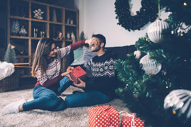 Woman closing eyes to boyfriend giving present - foto stock