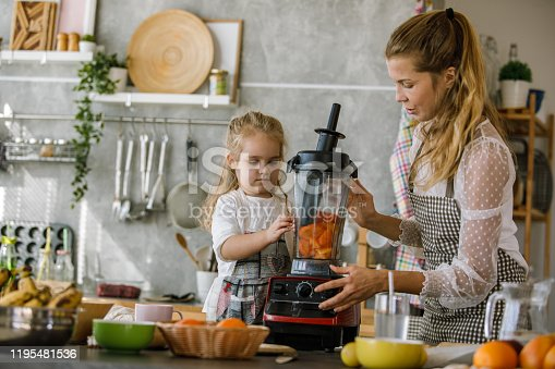 Copy space shot of young woman closing a blender after her toddler daughter assisted her in adding in freshly cut persimmons for a dessert they are preparing together.