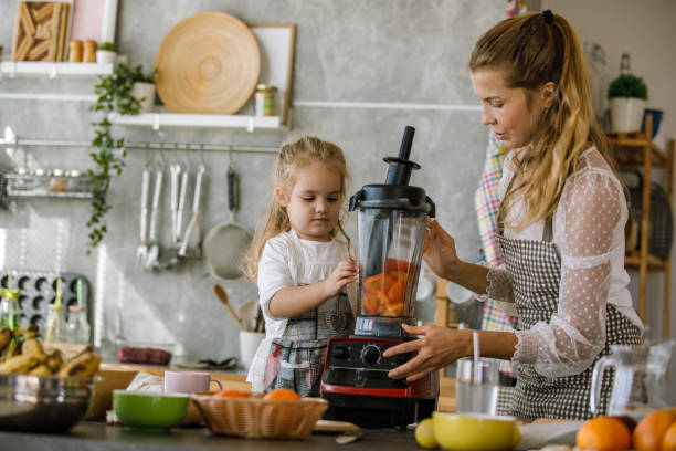 Woman closing the blender after adding the freshly cut persimmons stock photo