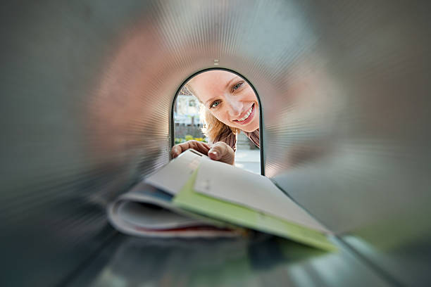 woman collecting mail from mailbox - mail stock photos and pictures