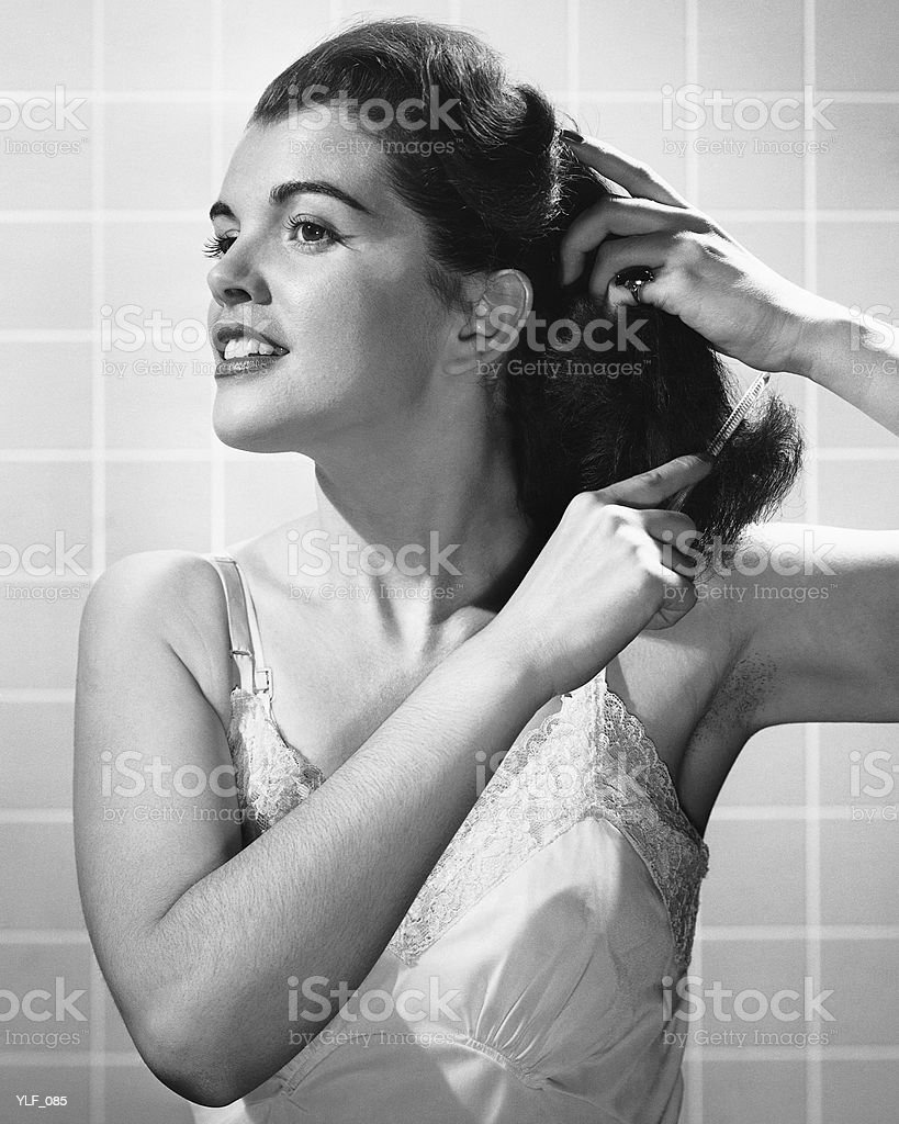 Woman combing hair royalty free stockfoto