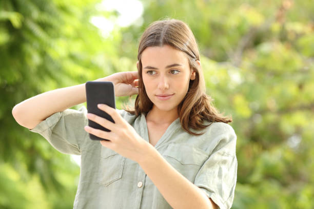 Woman combing hair using smartphone as a mirror stock photo