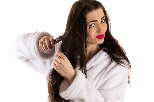 woman combing hair with sad face woman combing hair with sad face isolated on white background wet hair stock pictures, royalty-free photos & images