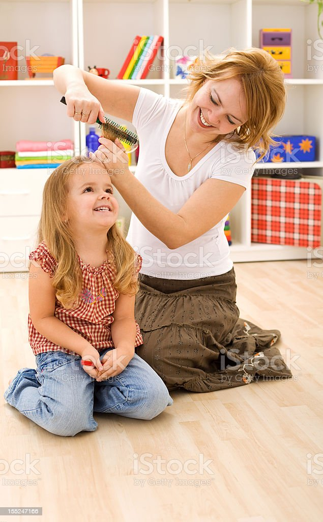 Woman combing little girls hair royalty-free stock photo