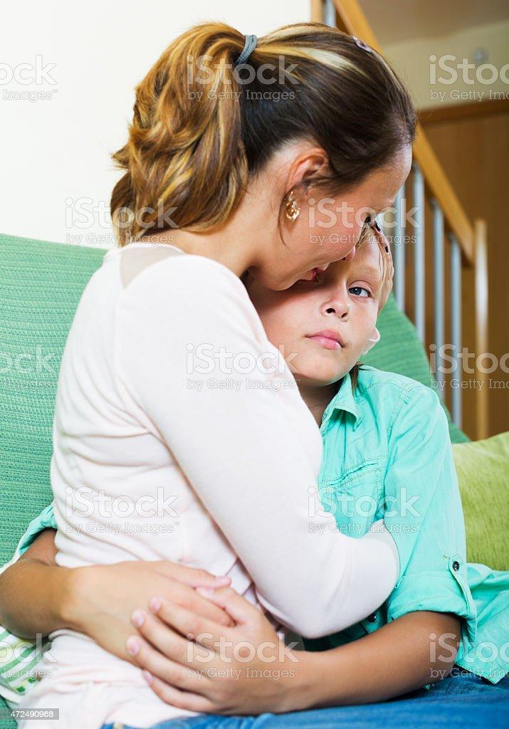 woman comforting crying teenager son stock photo