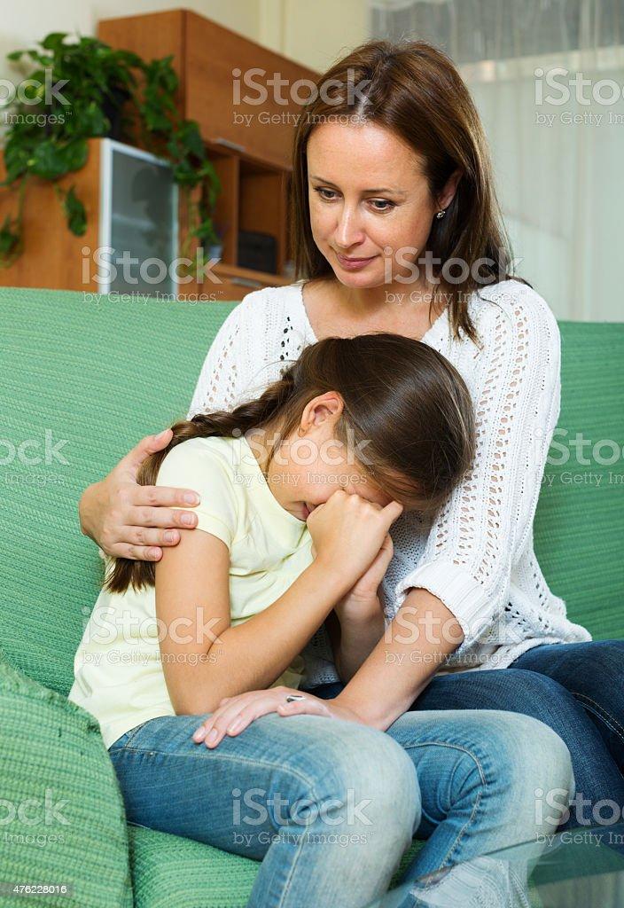 Woman comforting sad  crying daughter stock photo