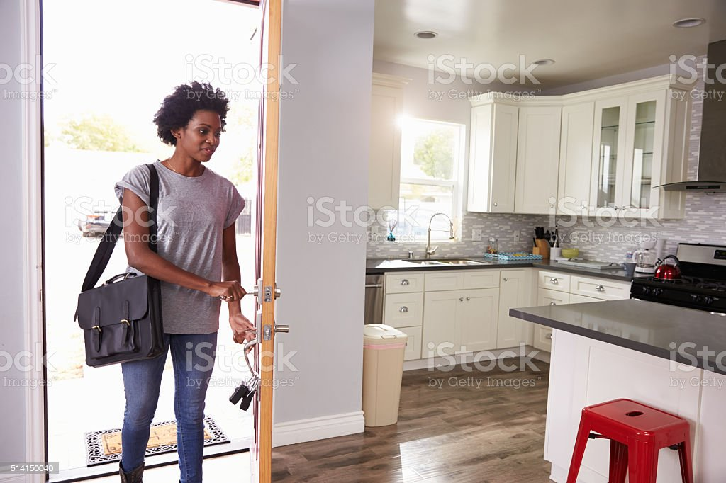 Woman Coming Home From Work And Opening Door Of Apartment stock photo
