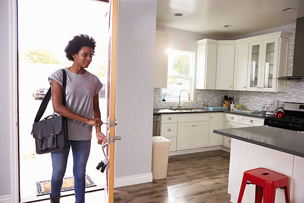 woman coming home from work and opening door of apartment - arrival stock photos and pictures