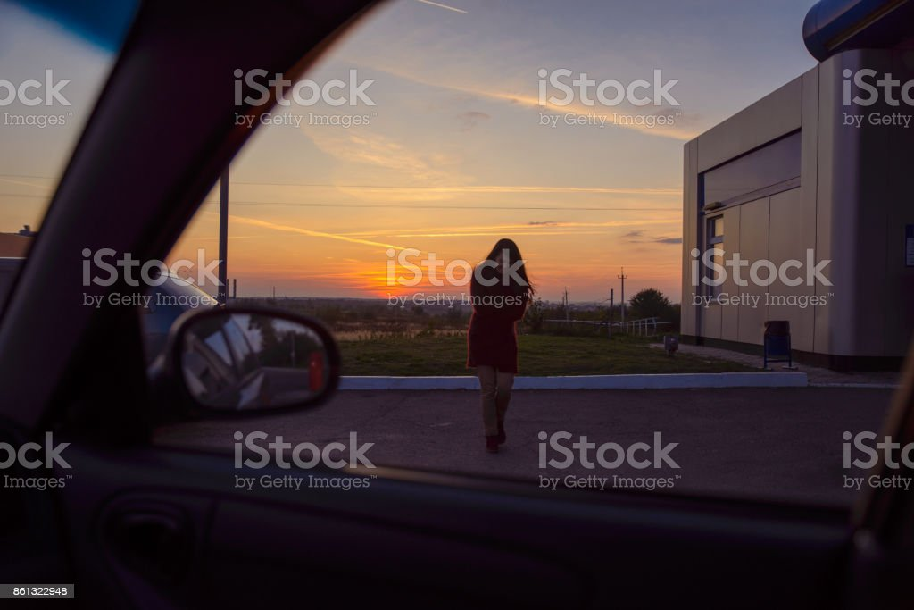 woman coming to a car with sunset on background stock photo