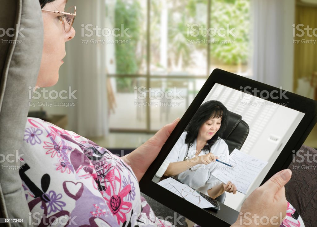Woman communicates with telemedicine doctor by digital tablet stock photo