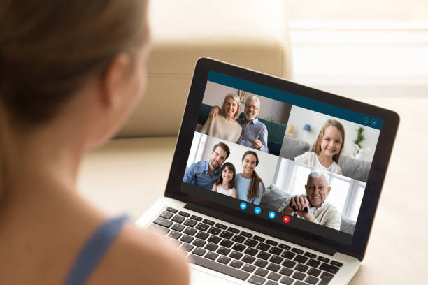 woman communicating with family using laptop and videoconference application - family gatherings stock pictures, royalty-free photos & images