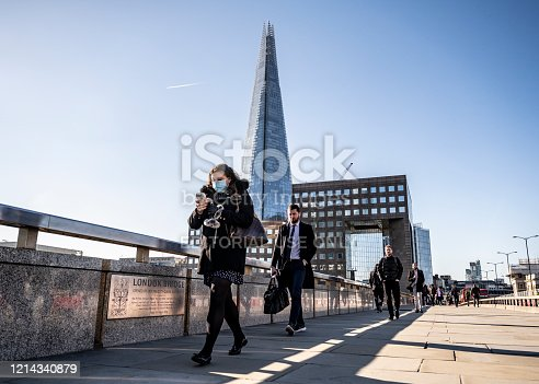 London, England, United Kingdom - March 23, 2019: Keyworkers commute to work over London Bridge as social distancing and work from home guidance take s effect