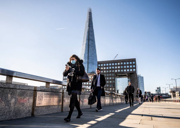 Woman commutes to work on London Bridge with protective face mask stock photo
