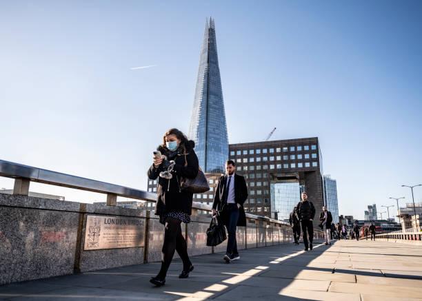 Frau pendelt mit schützender Gesichtsmaske zur Arbeit auf der London Bridge – Foto