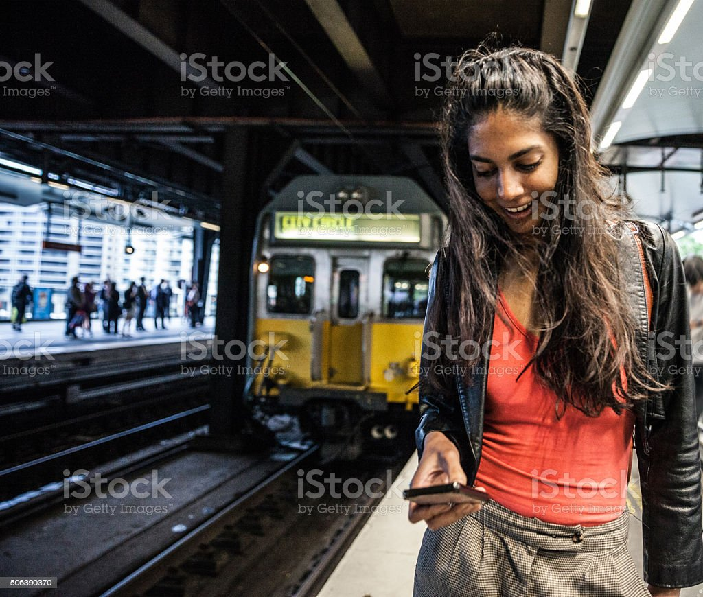 Woman commuting in a Sydney train and texting stock photo