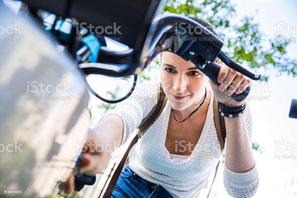 Woman commuting to work by bicycle in the city stock photo