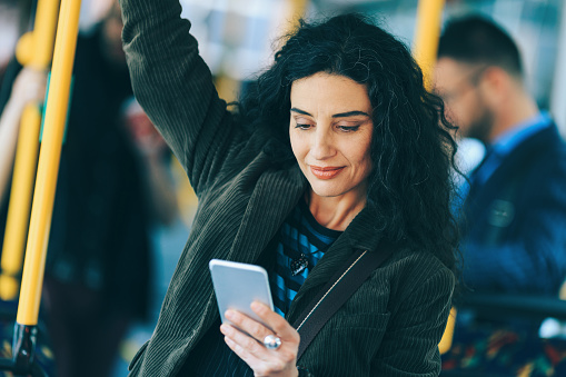 Woman commuting with public transport, looking at phone.