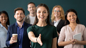 Friendly young company woman representative holds out her hand for handshake welcoming customer smiling looking at camera posing together with diverse colleagues, sales manager greeting client concept