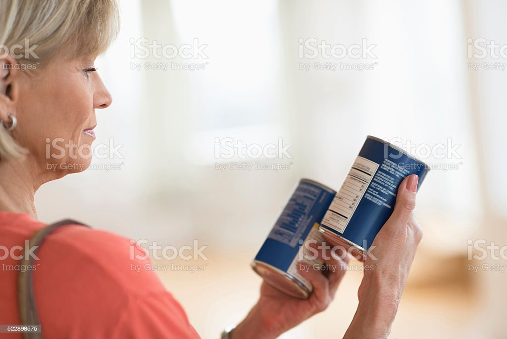 Woman Comparing Products In Shop Cropped image of woman comparing products in shop 50-59 Years Stock Photo
