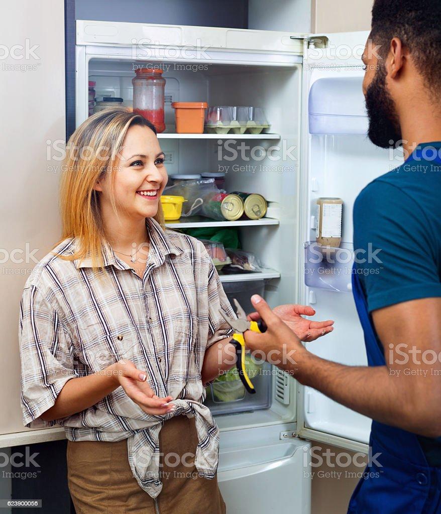woman complaining to black handyman on problems with fridge stock photo
