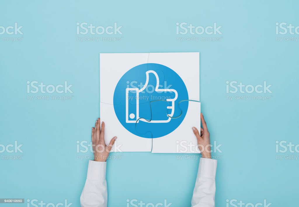 Woman completing a puzzle with thumbs up icon stock photo