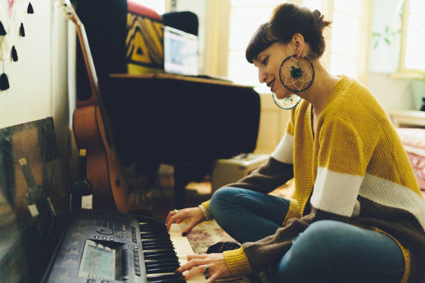 Woman composing music Hippie woman sitting on floor and playing on synthesizer keyboard player stock pictures, royalty-free photos & images