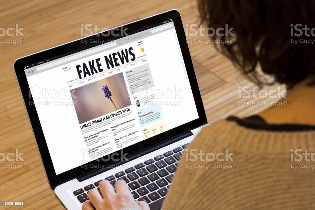 woman computer fake news stock photo