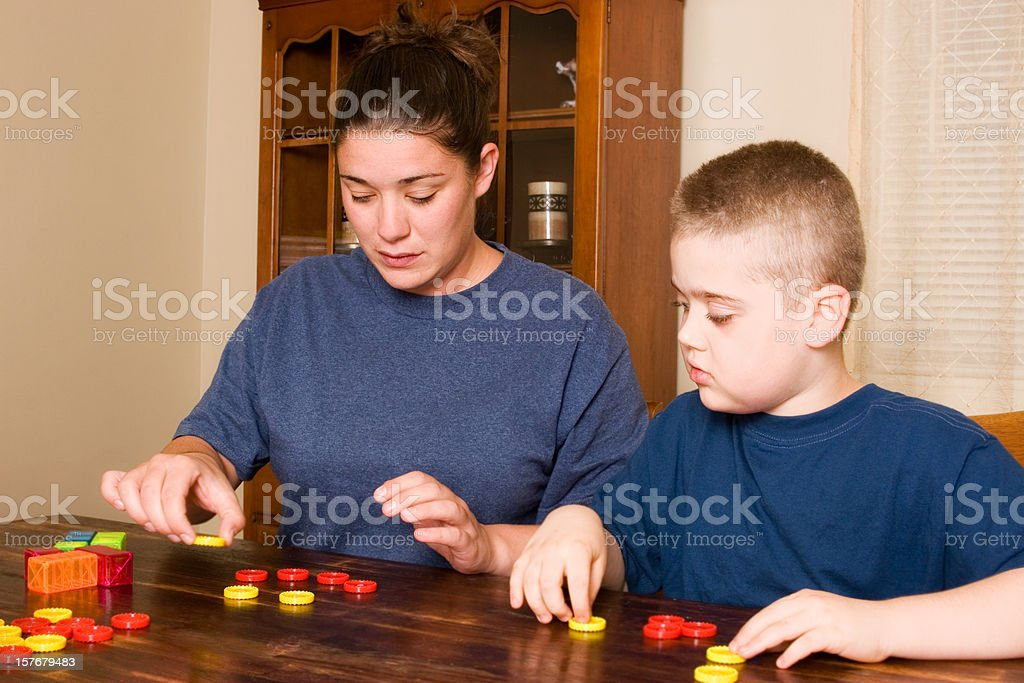 A woman conducting ABA therapy with a young boy at a table stock photo