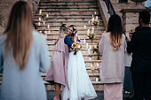 Loving mother embracing elegant bride at outdoors rustic cottage wedding ceremony in Europe