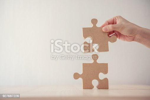 istock Woman connecting jigsaw puzzle on table wood, Business solutions, success and strategy concept 927687226