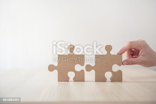 istock Woman connecting jigsaw puzzle on table wood, Business solutions, success and strategy concept 934883352