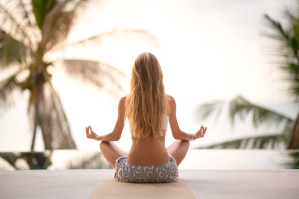 Woman connecting with Nature, Yoga Meditation Outdoor at Sunrise, Zen State stock photo