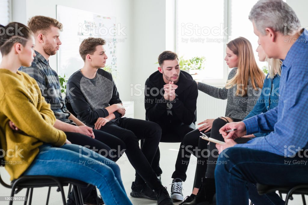 Woman consoling male friend in group therapy Woman consoling male friend during meeting. Men and women are with mature social worker during group therapy. They are sitting in lecture hall. 18-19 Years Stock Photo