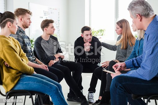 956725746 istock photo Woman consoling male friend in group therapy 1202791014