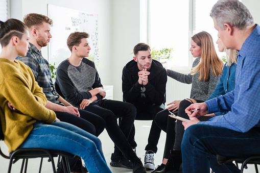 Woman Consoling Male Friend In Group Therapy Stock Photo - Download Image Now