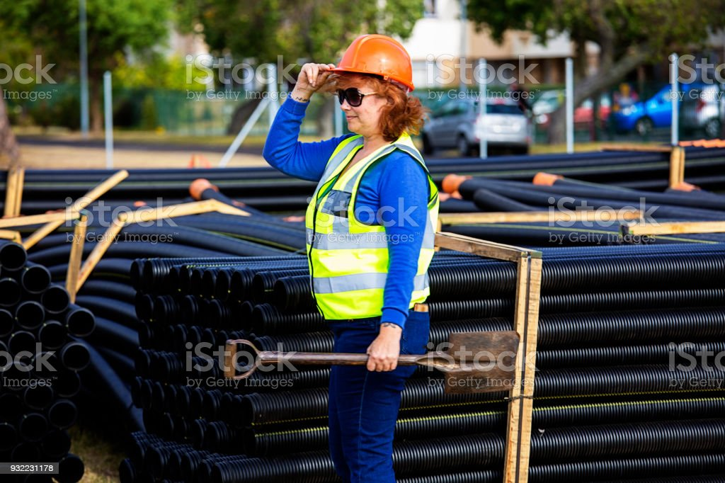 Woman construction worker in-front of tube pipes stock photo