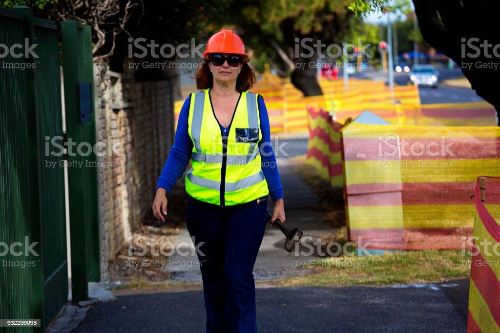 Woman construction worker walks along a sidewalk stock photo