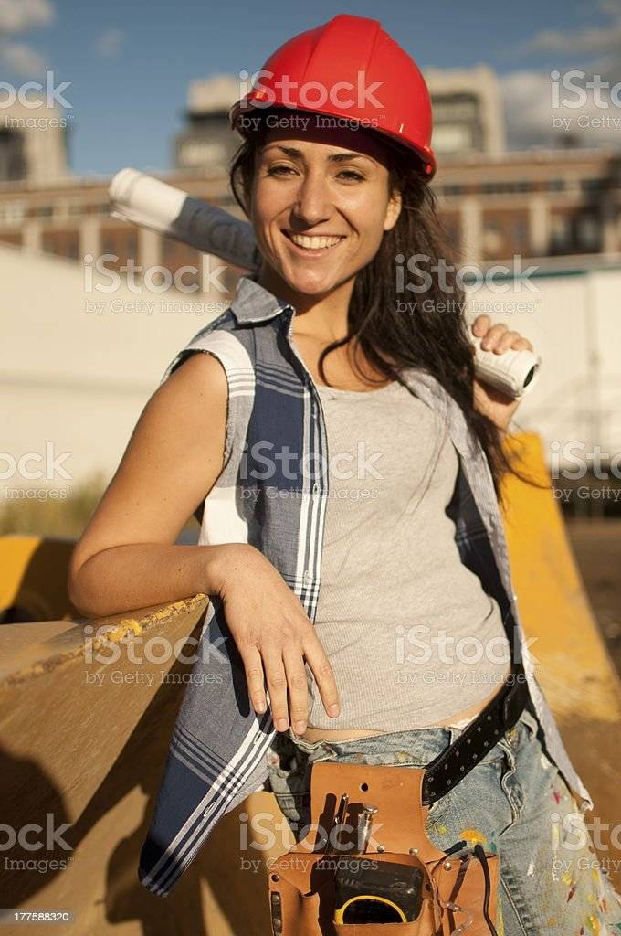 Woman construction worker wearing tank top with orange safety helmet royalty-free stock photo