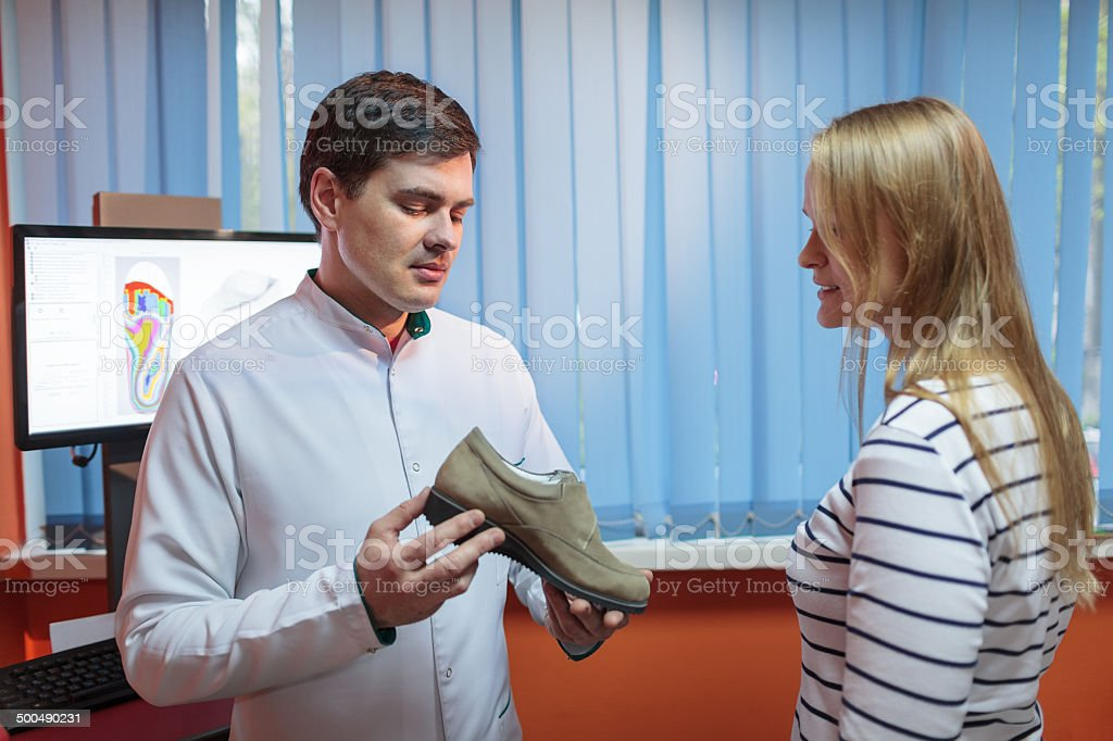Woman consulting foot doctor stock photo