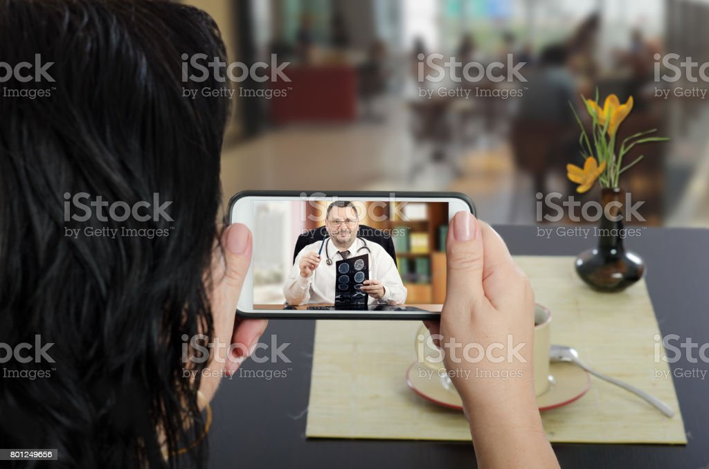 Woman contacts telemedicine doctor by mobile phone stock photo