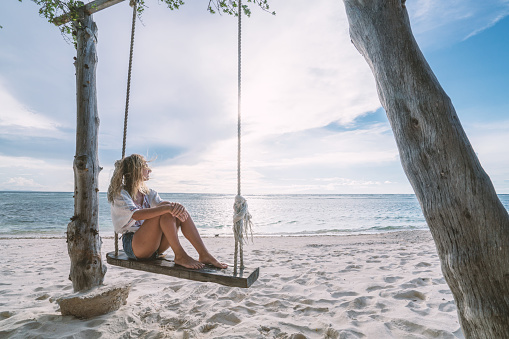 Woman contemplates horizon from swing by the beach, Indonesia