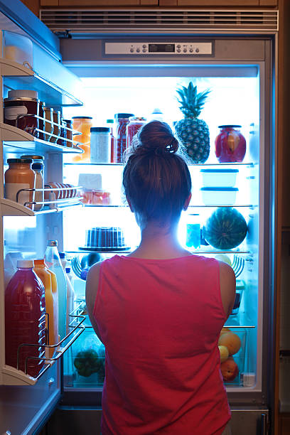 Woman Contemplating Midnight Snack late Night with Open Refrigerator A young caucasian woman standing in front of the open refrigerator at late night, contemplating and wondering about a midnight snack in a domestic home kitchen. She is dressed in a bath robe hungry and looking for food. A symbol of dieting lifestyle. Photographed in vertical format. midnight stock pictures, royalty-free photos & images